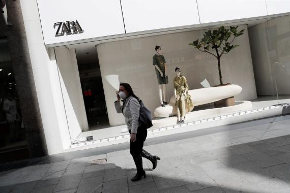 Una mujer camina por la calle con una tienda de fondo