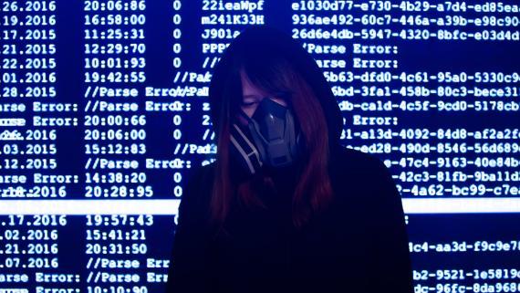 Una mujer con una máscara delante de una pantalla de datos