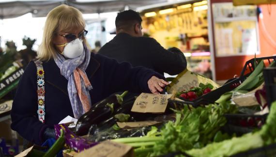 Una mujer con mascarilla compra verdura en un mercado de Turín (Italia)
