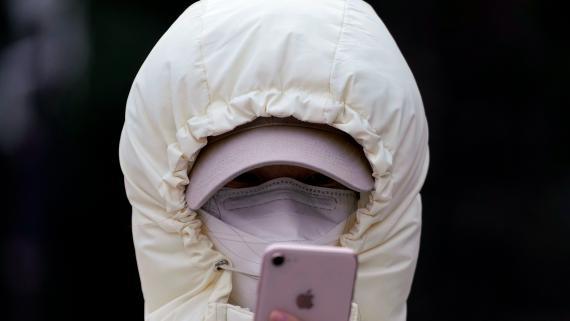 Una mujer con mascarilla mira su móvil en plena crisis de coronavirus.