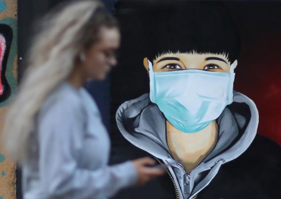 Una mujer mira su móvil mientras camina junto a un mural con un hombre llevando mascarilla.