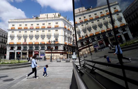 Una mujer pasea con un niño en la Puerta del Sol de Madrid durante el confinamiento por el coronavirus