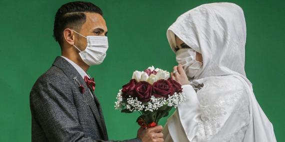 El novio palestino Mohamed Abu Daga y su novia Israa usan mascarillas en medio de la epidemia COVID-19, durante una sesión de fotos en un estudio antes de su ceremonia de boda.