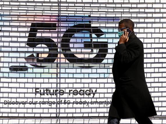 Un peatón pasa por delante de un anuncio que promociona la red de datos 5G en una tienda de teléfonos móviles en Londres en enero de 2020.