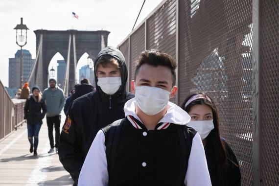Habitantes de Nueva York cruzan el puente de Brooklyn con mascarillas puestas, el lunes 16 de marzo de 2020 en Nueva York, Estados Unidos.
