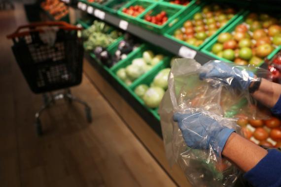 Una persona realiza la compra con guantes de protección por la pandemia del coronavirus