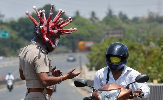 Un policía de Chennai (India) pide la documentación a un motorista mientras luce un casco que imita al coronavirus
