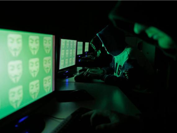 Gente frente a una pantalla que muestra la palabra 'cyber' en código binario, en esta imagen tomada en Zenica el 27 de diciembre de 2014.