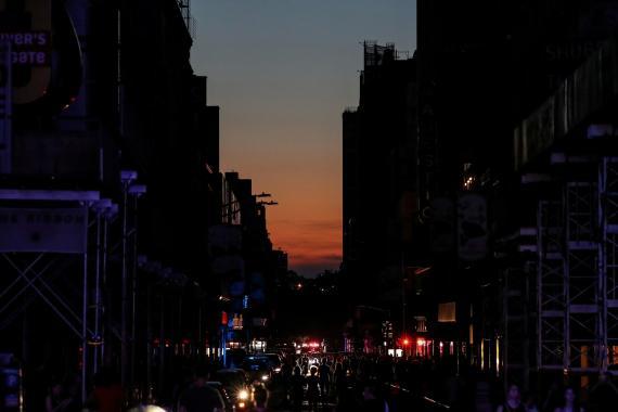 Un grupo de personas camina por una calle oscura cerca de Times Square durante un apagón en Manhattan, Nueva York