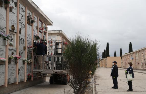 Padre e hija observan los nichos de un cementerio en Madrid, durante la pandemia de coronavirus