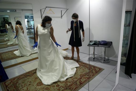 Una clienta y una empleada mantienen las medidas de seguridad en una tienda de vestidos de novia.