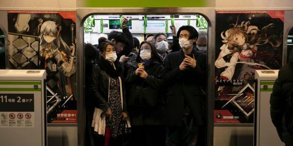 Gente desplazándose en transporte público con mascarillas en Tokio durante el coronavirus.