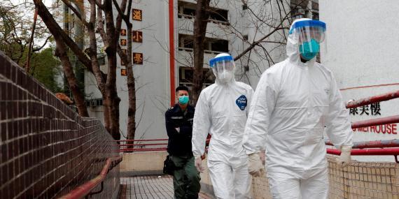 Trabajadores de la salud con equipo de protección en un complejo de viviendas en Hong Kong en febrero de 2020.