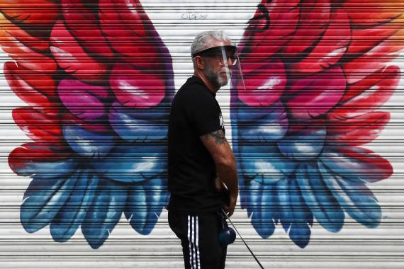 Un hombre pasea delante de una tienda cerrada en Madrid durante el confinamiento por el coronavirus