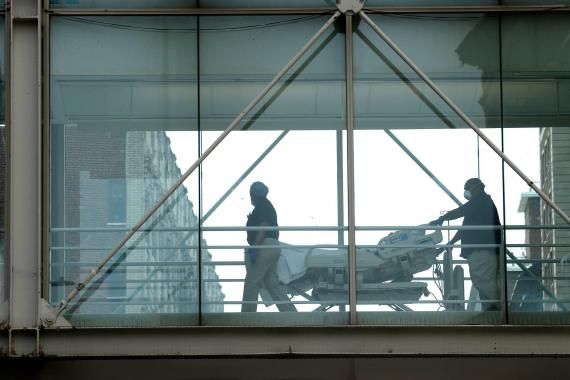 Medical staff move a patient on a gurney across the skyway at Mt. Sinai Morningside Hospital on May 18, 2020 in New York City.