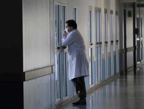 Un médico mira por una ventana
