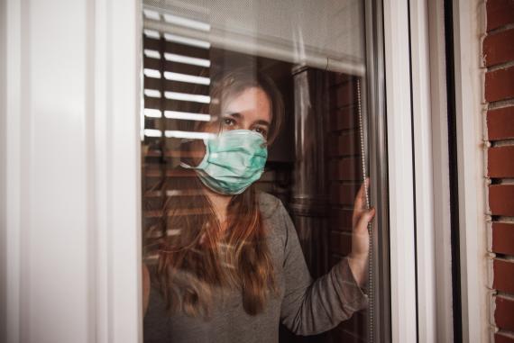 Mujer con mascarilla mira por una ventana