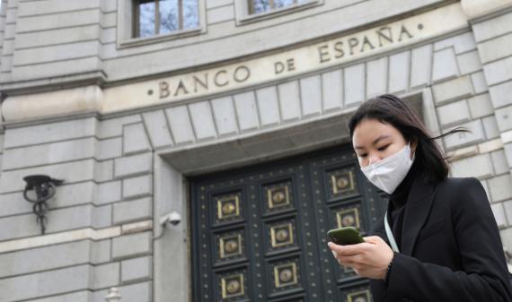 Una mujer con mascarilla pasa ante la sede del Banco de España en Madrid