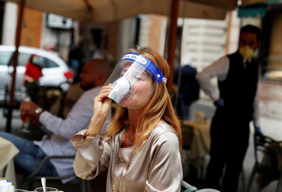 Una mujer con una pantalla facial se toma un café en Roma tras el desconfinamiento de algunas medidas en Italia