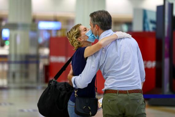 Una pareja se besa en el Aeropuerto Internacional de Dubái, Emiratos Árabes Unidos.
