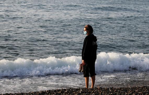 Una persona con mascarilla en la playa de la Barceloneta,  8 de mayo de 2020.
