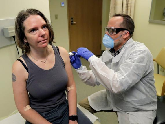 A pharmacist gives Jennifer Haller, left, the first shot in the first-stage safety study clinical trial of a potential vaccine for COVID-19.