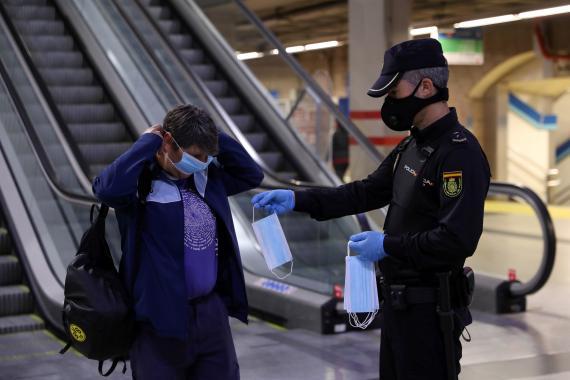 Policía entregando mascarillas a los viajeros de transporte público.