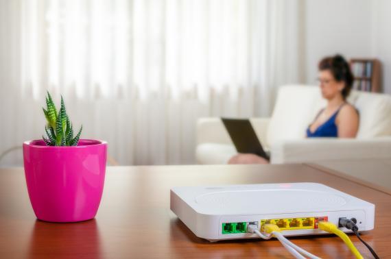 Un router con una mujer de fondo con un ordenador