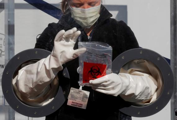 Una trabajadora recoge muestras de un paciente infectado por el coronavirus