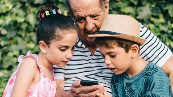 Un abuelo mira el móvil con sus dos nietos.