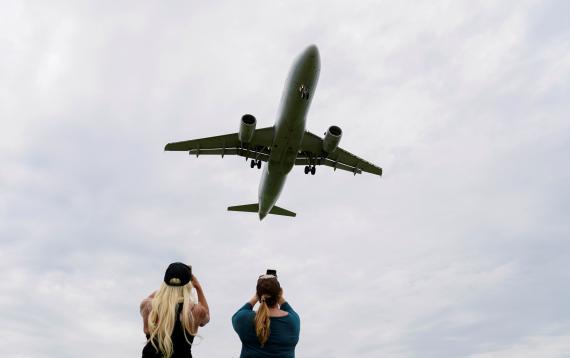 Pasajeros fotografían el aterrizaje de un avión en el Aeropuerto Nacional Ronald Reagan de Washington, en EEUU.