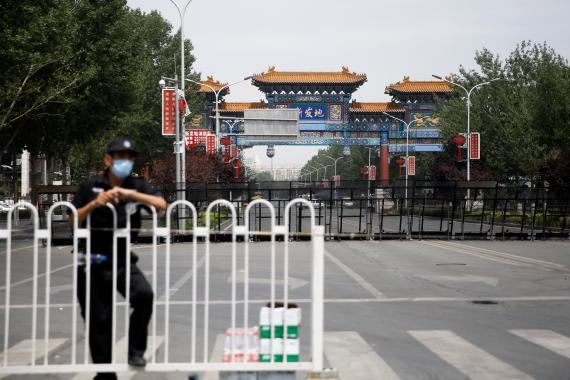 Un oficial de seguridad bloquea la entrada al mercado mayorista de Xinfadi en Pekín.