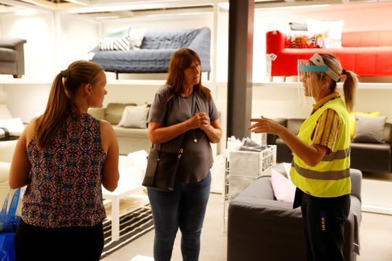 Una empleada de Ikea protegida con una mascarilla facial atiende a dos clientas tras la reapertura de los establecimientos en Londres