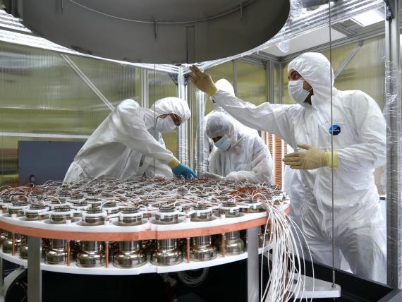 Expertos construyen la matriz superior de tubos fotomultiplicadores, que detectan destellos de luz a partir de interacciones de partículas.