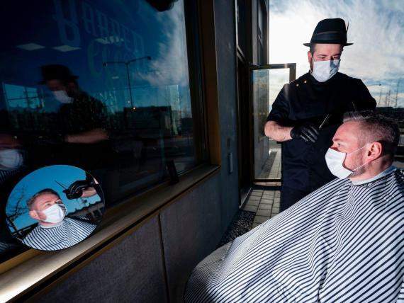 El peluquero Abed Khankan le corta el pelo a un cliente al aire libre como precaución en medio de la nueva pandemia de coronavirus, 17 de abril de 2020 en Malmo, Suecia.