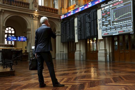 Un hombre en el parqué de la Bolsa de Madrid mirando las pantallas del Ibex 35
