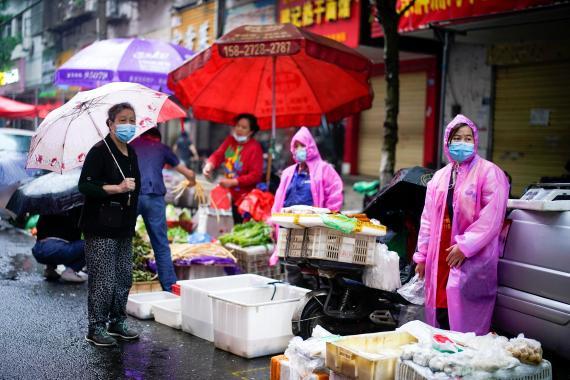 Residentes con mascarillas en un mercado callejero en Wuhan, China.