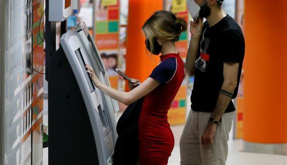 Una mujer con mascarilla retira efectivo de un cajero automático en un centro comercial de Kiev (Ucrania)