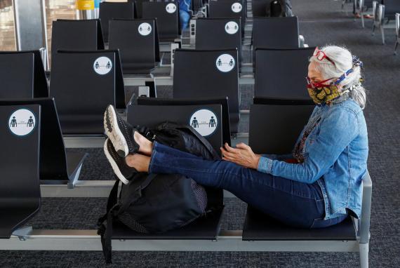 Una mujer mira el móvil en un aeropuerto