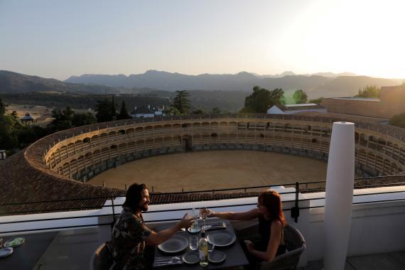 Una pareja de turistas brinda en la terraza de un hotel de ronda tras el alivio de las restricciones por el coronavirus.