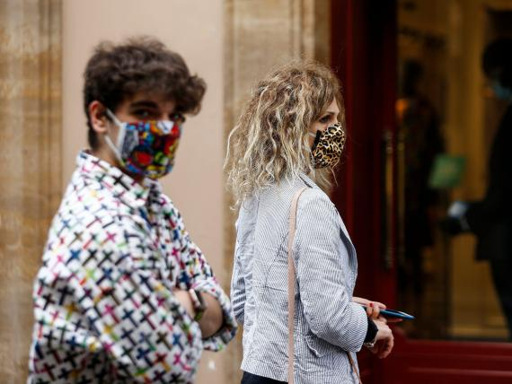 People wearing sanitary masks walk in Via Condotti shopping street, in Rome, Italy, Monday, May 18, 2020. Italy is slowly lifting sanitary restrictions after a two-month coronavirus lockdown. (Cecilia Fabiano/LaPresse via AP)