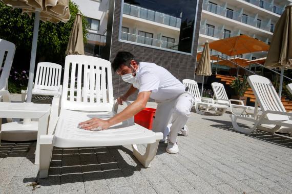 Un trabajador desinfecta una zona de piscinas en un hotel de Palma de Mallorca