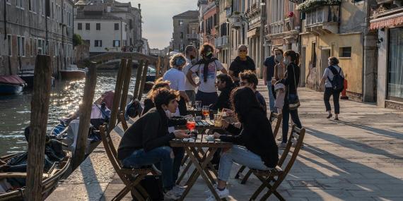 Los venecianos toman el aperitivo en un bar el 20 de mayo de 2020. Restaurantes, bares, cafés, peluquerías y otras tiendas han reabierto, sujetos a medidas de distanciamiento social, después de más de dos meses.