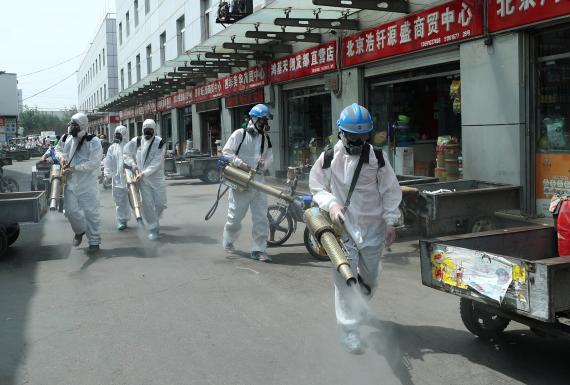 Voluntarios del equipo de rescate de Blue Sky desinfectan el mercado mayorista de Yuegezhuang en Beijing en medio del rebrote de coronavirus.