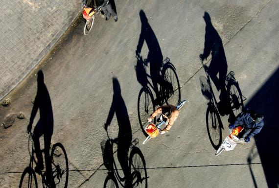 Ciclistas montan sus bicicletas en el centro de Pekín.