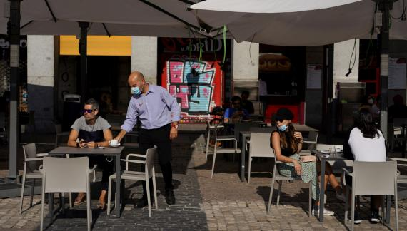 Un camarero con mascarilla sirve un café en una terraza de Madrid