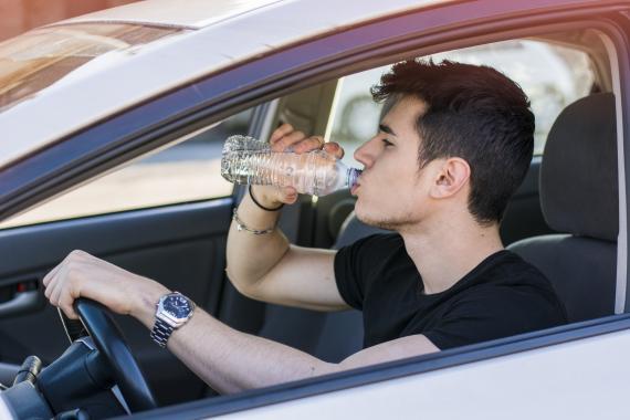 Un chico bebiendo agua en el coche