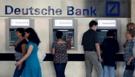 Clientes sacando dinero de cajeros automáticos en una sucursal de Deutsche Bank en Munich (Alemania)