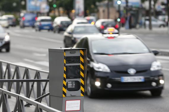 Un coche pasa un radar de tráfico.