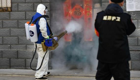 Un funcionario desinfecta la entrada de una vivienda en Mongolia Interior (China)
